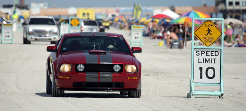 red mustang driving down beach
