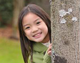 Photo of girl look around a tree