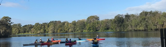 Kayakers on the water learning about conservation lands